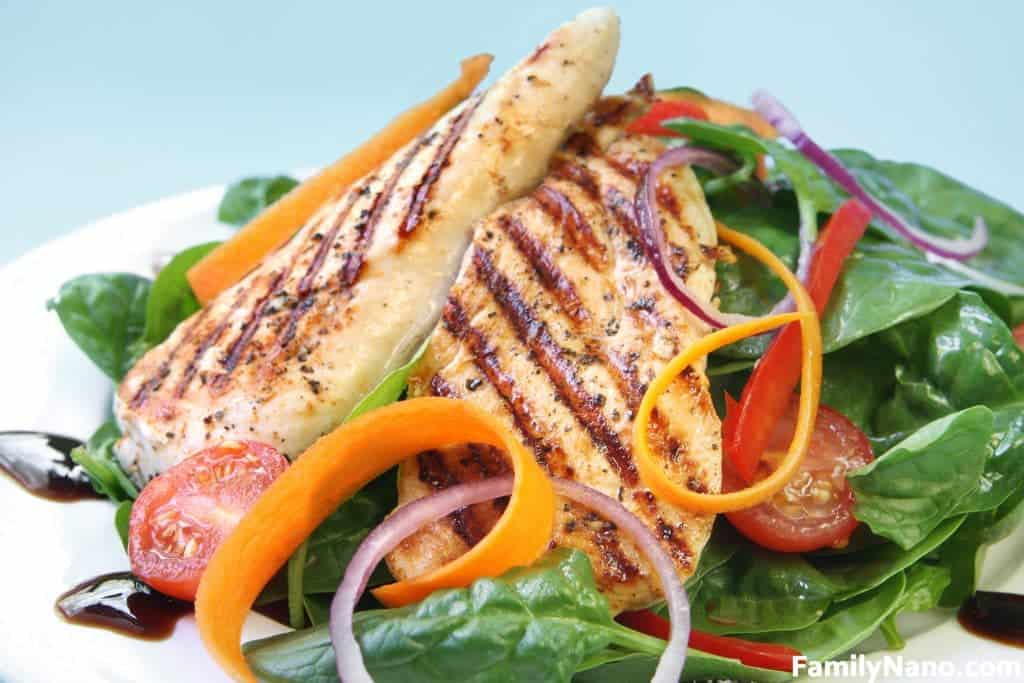 Grilled chicken breast with a spinach salad with a balsamic reduction.