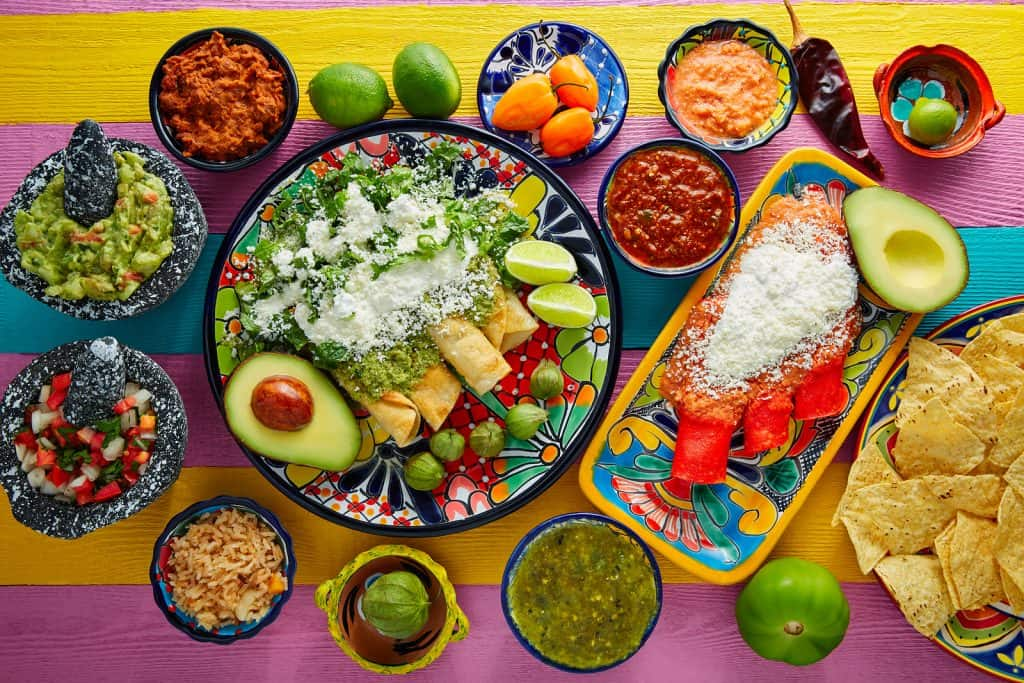 Green and red enchiladas with mexican sauces mix in colorful tab