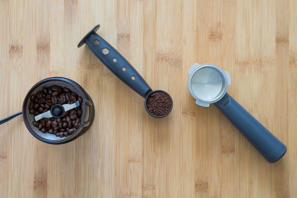 A coffee grinder with beans and scoop with grounds.
