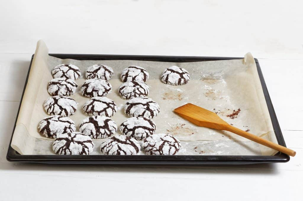 Homemade chocolate crinkle cookies on a baking sheet